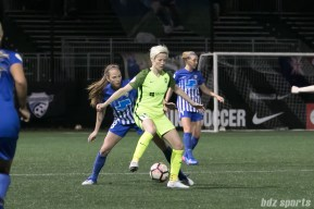 Reign FC's Megan Rapinoe #15 shields the ball from Breakers' Julie King #8.