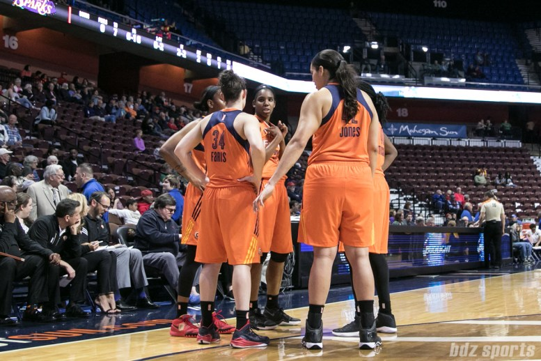 Sun's Kelly Faris #34 and Brionna Jones #42 huddle with teammates.