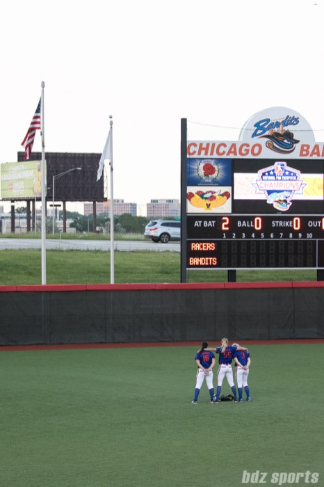 Chicago Bandits outfielders Natalie Hernandez (16), Brenna Moss (55), and Emily Crane (3) share a moment before the playing of the national anthem.