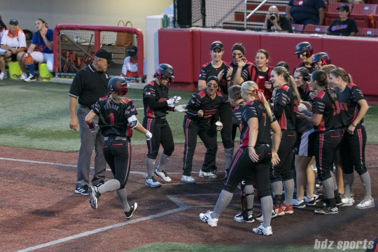 Akron Racers second baseman Ashley Thomas (1) is greeted by her teammates at home plate after hitting a two-run homer.