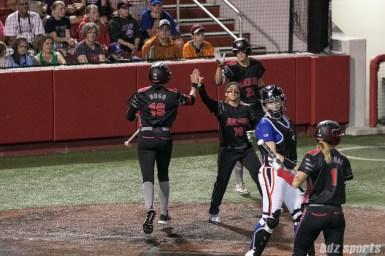 Akron Racers second baseman Alex Hugo (16) high fives third baseman Kelley Montalvo (10) after scoring a run.