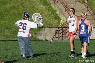 Boston Storm goalie Rachel Vallarelli (26) and midfielder Vicki Gaveline (4) stick high five.