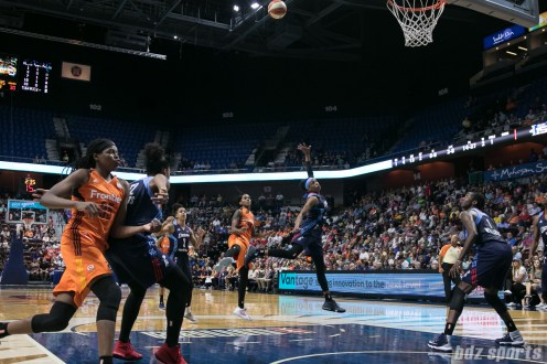 Connecticut Sun guard Courtney Williams (10) and Atlanta Dream guard Brittney Sykes (7) look on as Williams' shot heads to the basket.