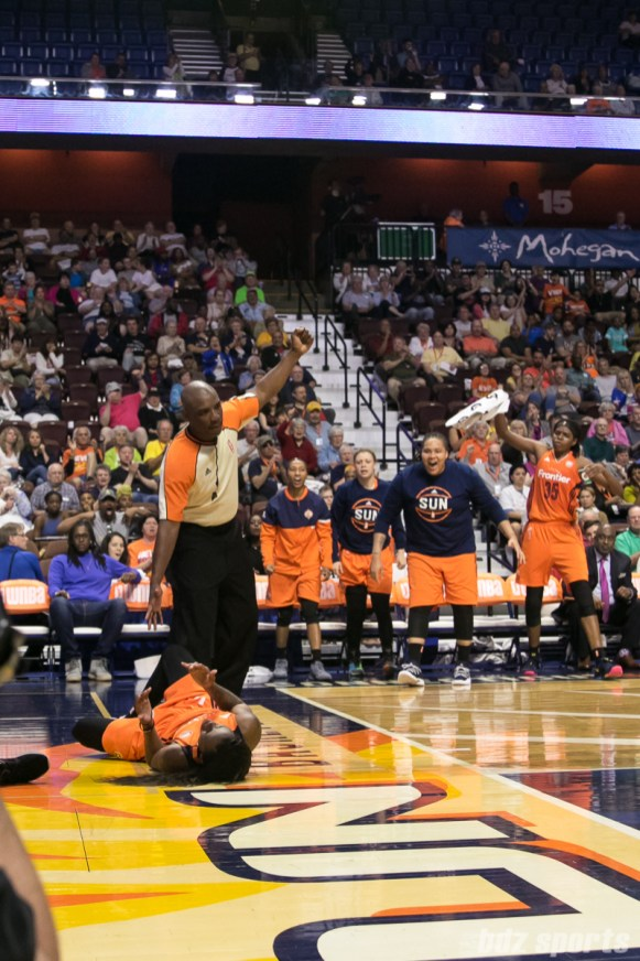 The Connecticut Sun bench is fired up after teammate Courtney Williams (on the ground) makes her layup and gets the foul call.