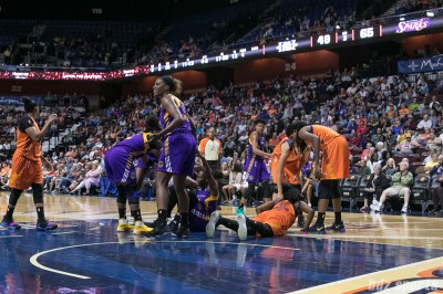 Los Angeles Sparks guard Chelsea Gray (12) and Connecticut Sun forward Shekinna Stricklen (40) are helped up by their teammates after colliding while going for the ball.