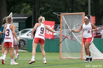 Boston Storm midfielder Charlie Finnigan (9) and attacker Bre Hudgins (11) tap sticks after Finnigan's goal.