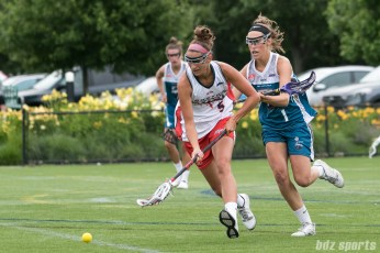 Boston Storm midfielder Tanner Guarino (5) scoops up a ball while being defended by Philadelphia Force Alyssa Murray (1).