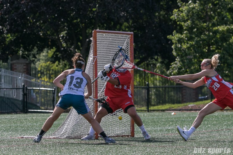 Philadelphia Force attacker Becky Lynch (13) slips in a shot between the legs of Boston Storm goalie Jackie Chirco (23).