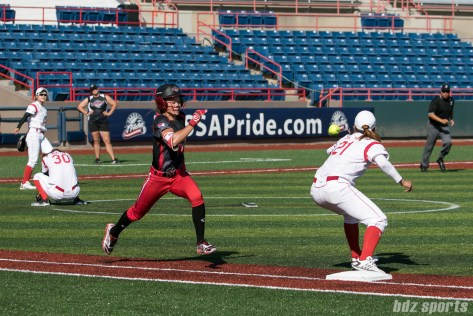 The ball beats out Akron Racers outfielder Kristen Wycoff (11) at first base.
