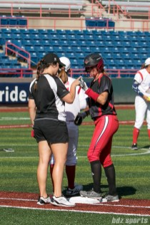 Akron Racers second baseman Ashley Thomas (1) celebrates her base hit with assistant coach Charlotte Morgan.