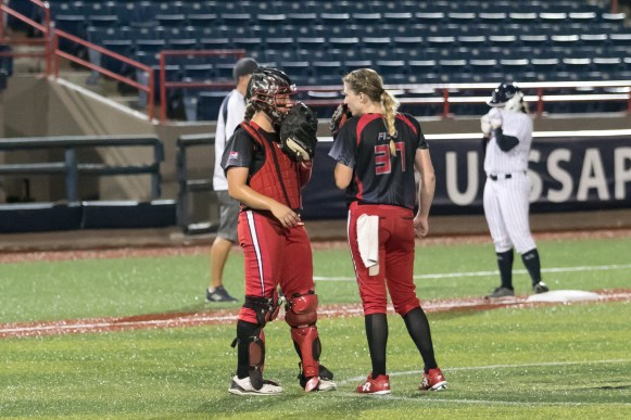 Akron Racers catcher Griffin Joiner (13) talks to pitcher Rachele Fico (37) on the mound.
