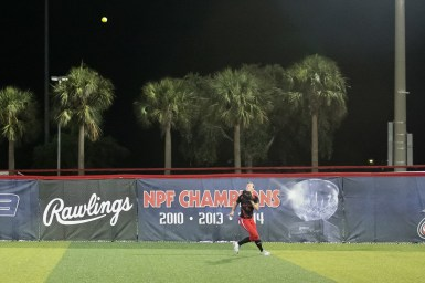 Akron Racers outfielder Megan Geer (14) tracks the ball to make the catch.