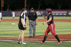 Akron Racers infielder Maddy Grimm (23) high fives assistant coach Charlotte Morgan after safe at first base.