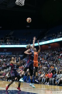 Connecticut Sun guard Jasmine Thomas (5) takes a shot over the arm of Washington Mystics forward Elena Delle Donne (11).
