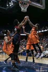 Washington Mystics center Krystal Thomas (34) and Connecticut Sun guard Courtney Williams (10) reach up to grab rebound.