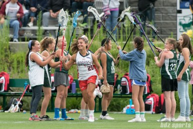 Boston Storm attacker Caitlin Villareal (20) runs through the tunnel of sticks as her name is called during starting lineup announcements.