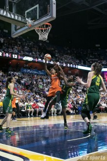 Connecticut Sun guard Courtney Williams (10) battles with Seattle Storm forward Crystal Langhorne (1) for the rebound.