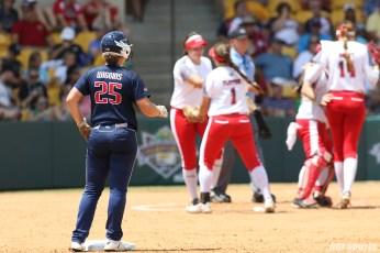USSSA Pride Megan Wiggins (25) looks on as the Scrap Yard Dawgs infielders huddle together