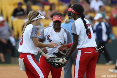 Scrap Yard Dawgs outfielders Allexis Bennett (43), Nerissa Myers (15), and Kayla Winkfield (9) slap hands before the start of the inning