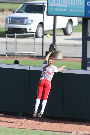 The ball is just out of reach of Scrap Yard Dawgs outfielder Morgan Zerkle (28)