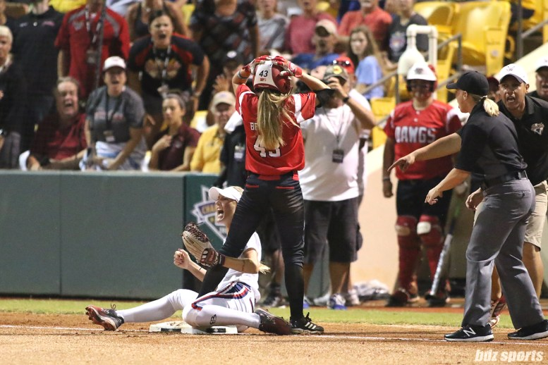 Scrap Yard Dawgs outfielder Allexis Bennett (43) is in disbelief as she is ruled tagged out at third base