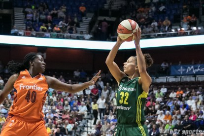 Seattle Storm forward Alysha Clark (32) possesses the ball for the Storm while being defended by Connecticut Sun forward Shekinna Stricklen (40).