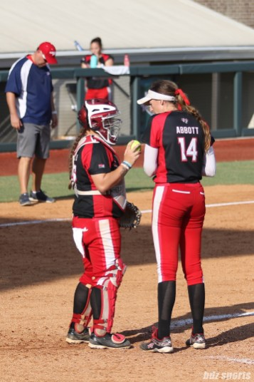 Scrap Yard Dawgs catcher Taylor Edwards (25) and pitcher Monica Abbott (14) talk at the mound