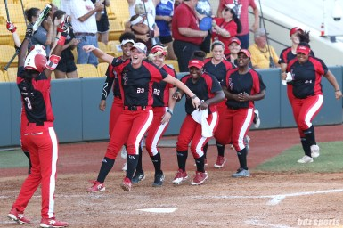The Scrap Yard Dawgs gather at home plate to greet teammate Meagan May Whitley (not pictured) after her solo home run in the top of the 7th inning