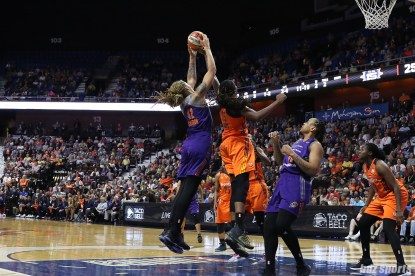 Phoenix Mercury center Brittney Griner (42) grabs the rebound over the arm of Connecticut Sun center Jonquel Jones (35)