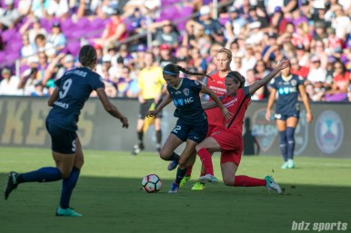North Carolina Courage forward Ashley Hatch (12) looks to get past an oncoming slide tackle from a Portland Thorns FC defender