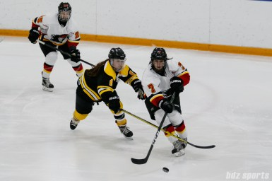 Calgary Inferno forward Brittany Esposito (7) dishes off a pass while Boston Blades defender Sato Kikuchi (8) defends