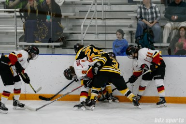 Boston Blades players Kristina Brown (24) and Courtney Turner battle Calgary Inferno forward Laura Dostaler (2) for the puck