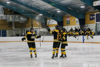 Boston Blades players Dru Burns (7), Meghan Grieves (17) and Michelle Ng (5) celebrate Grieves' goal