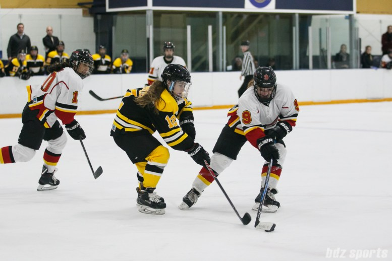 Boston Blades forward Casey Stathopoulos (12) defends against Calgary Inferno forward Dakota Woodworth (9)