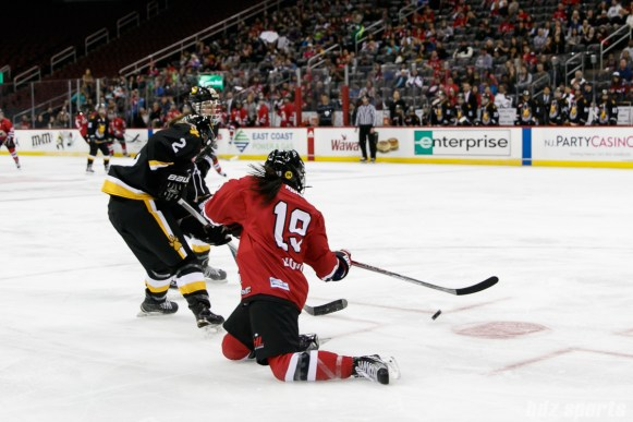 Metropolitan Riveters forward Miye D'Oench (19) attempts to play the puck while sliding on her knees