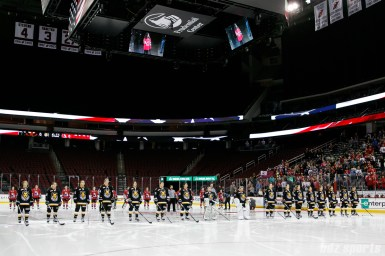 The Metropolitan Riveters and Boston Pride stand for the singing of the national anthem