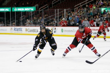 Boston Pride forward Dana Trivigno (8) controls the puck while Metropolitan Riveters defender Kelsey Koelzer (55) defends