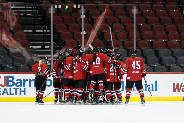 The Metropolitan Riveters huddle around goalie Katie Fitzgerald (35) after defeating the Boston Pride 4 - 1 in their season opener
