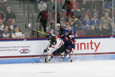 Team USA forward Hilary Knight (21) gets crowded into the boards by Team Canada defender Jocelyne Larocque (3)
