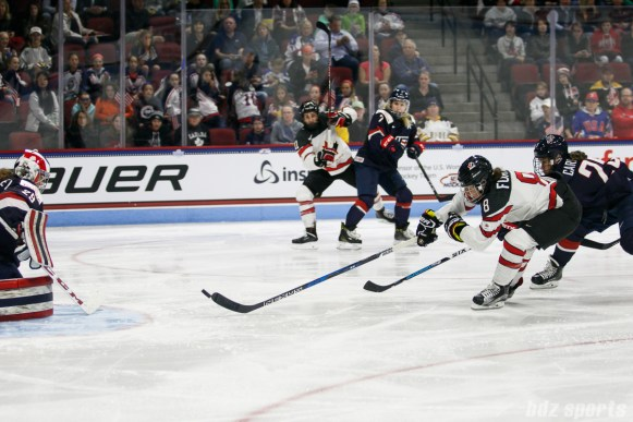 Team Canada defender Laura Fortino (8) gets enough of her stick on the puck to deflect the puck in for Team Canada's second goal of the game