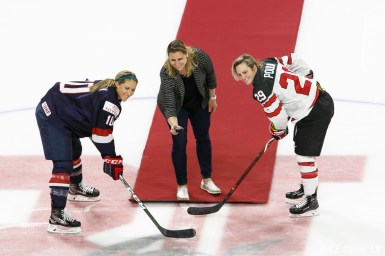 Team USA captain Meghan Duggan (10) and Team Canada captain Marie-Philip Poulin (29) take the ceremonial face off with the puck dropped by USA Olympic gold medalist Angela Ruggiero