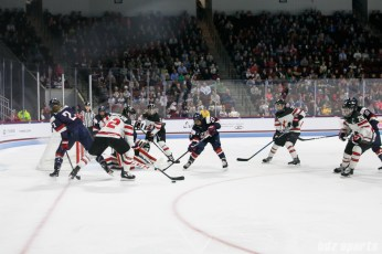 Team Canada defender Meaghan Mikkelson (12) keeps the puck in play in front of the Team USA goal