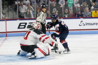 Team Canada goalie Genevieve Lacasse (31) comes up with a stop against Team USA forward Kendall Coyne (26)