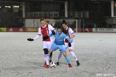 FC Twente forward Joelle Smits (9) tries to fend off two Ajax defenders