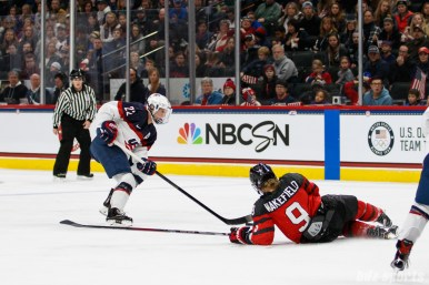 Team Canada forward Jennifer Wakefield (9) slides to intercept the puck from Team USA defender Kacey Bellamy (22)