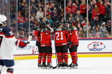 Team Canada players Natalie Spooner (24), Jocelyne Larocque (3), Haley Irwin (21), and Lauriane Rougeau (5) huddle prior to the restart of play