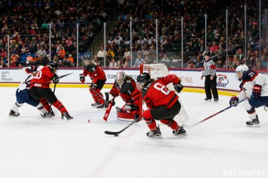 Team Canada defender Laura Fortino (8) looks to get the puck out of danger