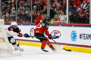 Team Canada defender Meaghan Mikkelson (12) controls the puck while being pressured by Team USA forward Dani Cameranesi (24)