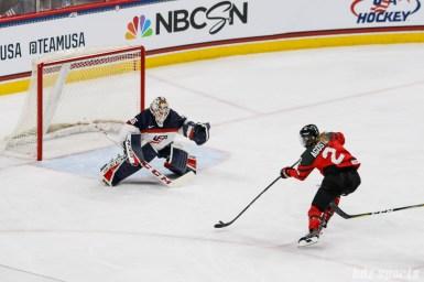 Team Canada forward Meghan Agosta (2) takes a shot on Team USA goalie Maddie Rooney (35)