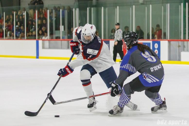 Team USA defender Megan Keller (5) attempts to get past Team NWHL forward Miye D'Oench (9)